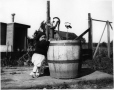 Child at water pump and barrel, St. Jovite(?), QC, about 1915 (MP-0000.589.392)